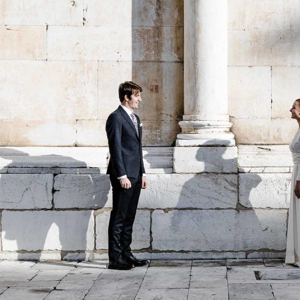 valentina esposito fotoreporter matrimoni sposi che si guardano in piedi sfondo facciata laterale chiesa