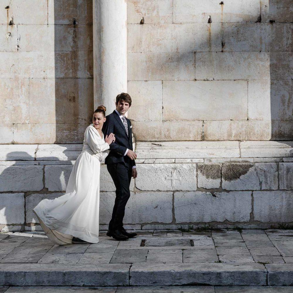 valentina esposito fotoreporter matrimoni sposi che guardano fotografo in piedi sfondo facciata laterale chiesa