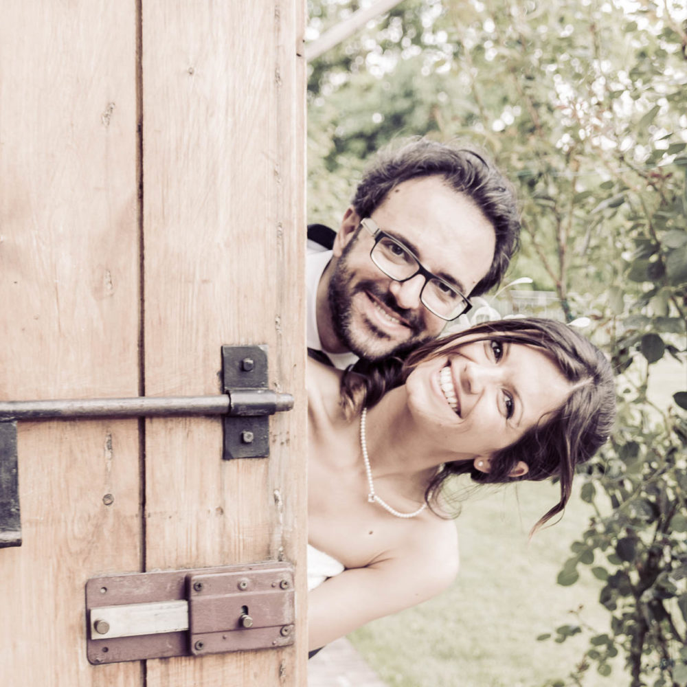 valentina esposito fotoreporter matrimoni facce sposi che spuntano da dietro una porta di legno ridono