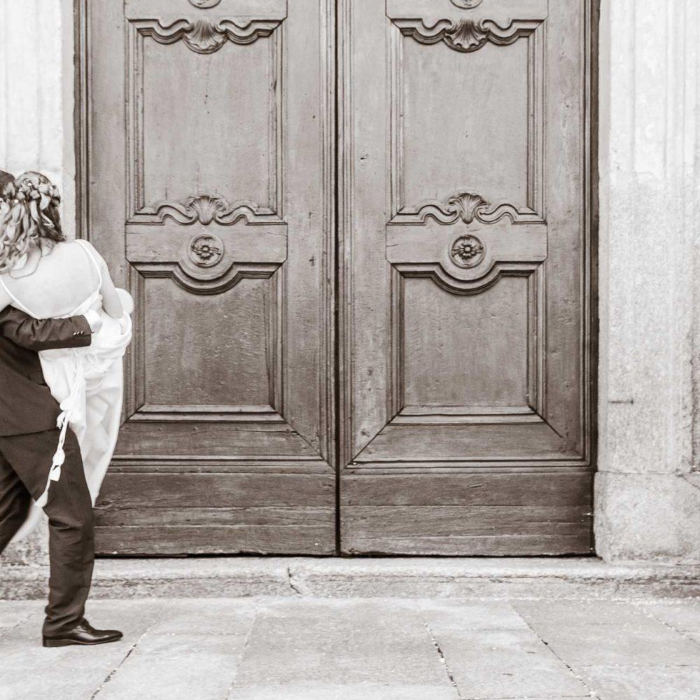 valentina esposito fotoreporter matrimoni sposo che prende in braccio la sposa di fronte a portone monumentale