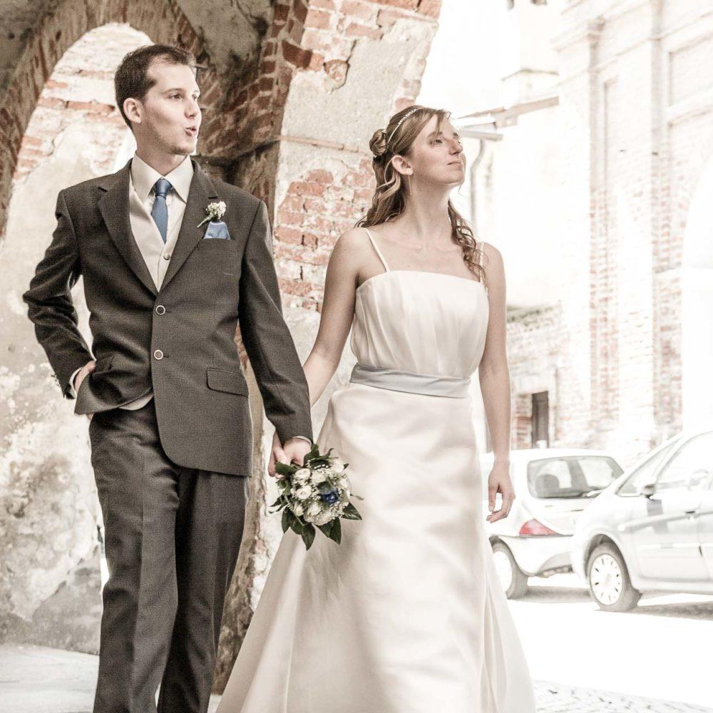 valentina esposito fotoreporter matrimoni sposi camminano scherzosamente sotto portico medievale