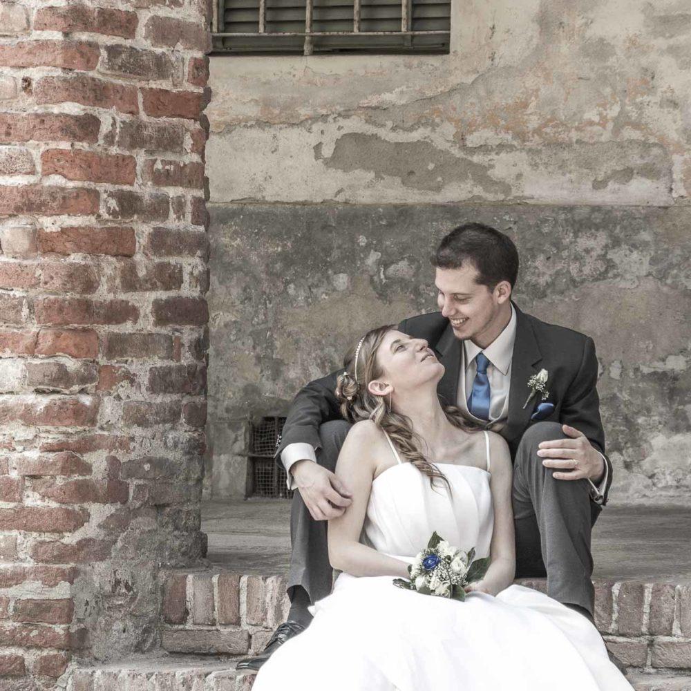 valentina esposito fotoreporter matrimoni sposi che si guardano teneramente seduti sotto portico medievale