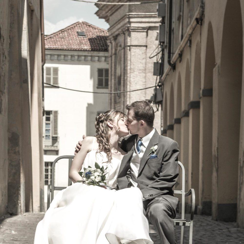valentina esposito fotoreporter matrimoni sposi seduti su panchina in mezzo alla strada si baciano